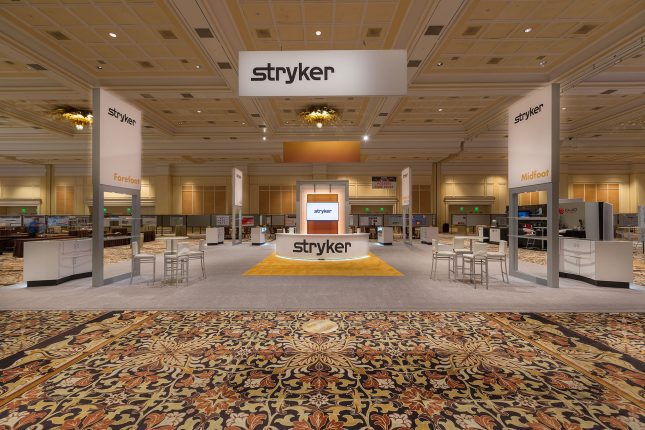 A centered photo of the Stryker booth at ACFAS 2017 with hanging banner, welcome counter with LCD screen, and four vertical signs all with the Stryker logo.