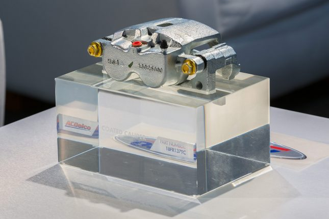 An ACDelco Caliper 18FR1379C on display atop a clear, acrylic block.
