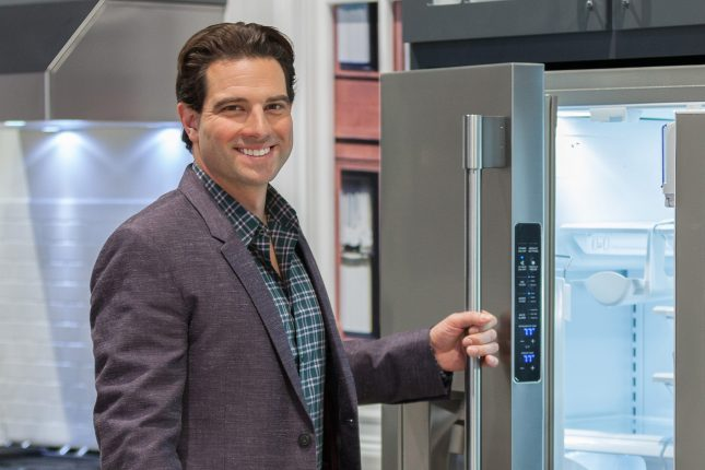 HGTV's Scott McGillivray, a white male smiling in a grey suit jacket opening a stainless steel refrigerator with illuminated white interior in the KBIS 2016 Electrolux exhibit.