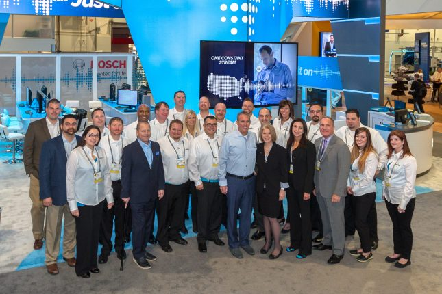 A team photograph of 25 on grey carpet in front of a blue and grey modern trade show exhibit.