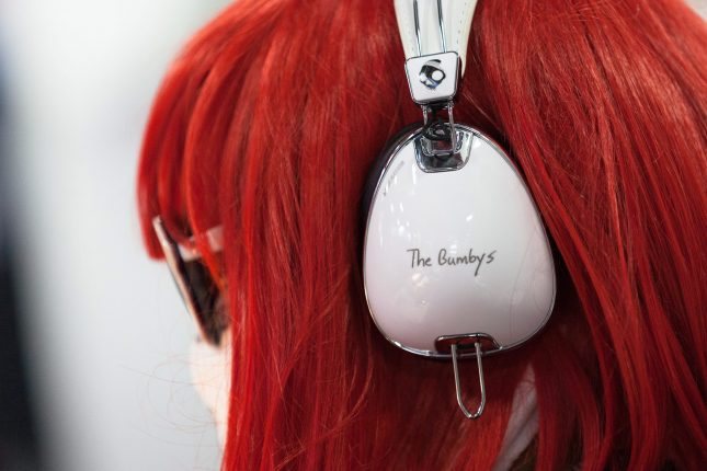 "A side view of a red-haired woman with sunglasses and white headphones with ""The Bumby's"" written on the side."