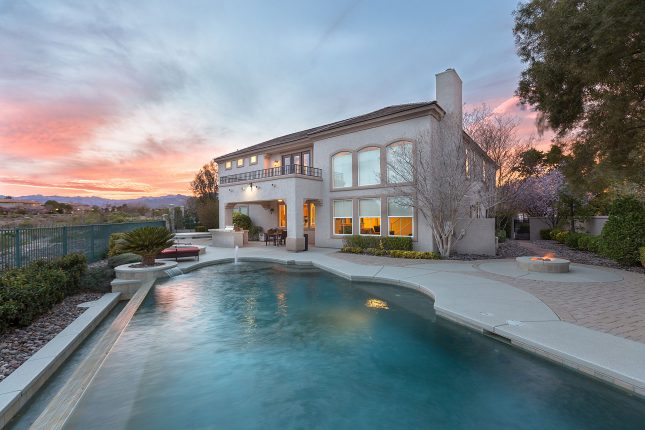 The swimming pool of a southwestern-style two-story home at sunset.
