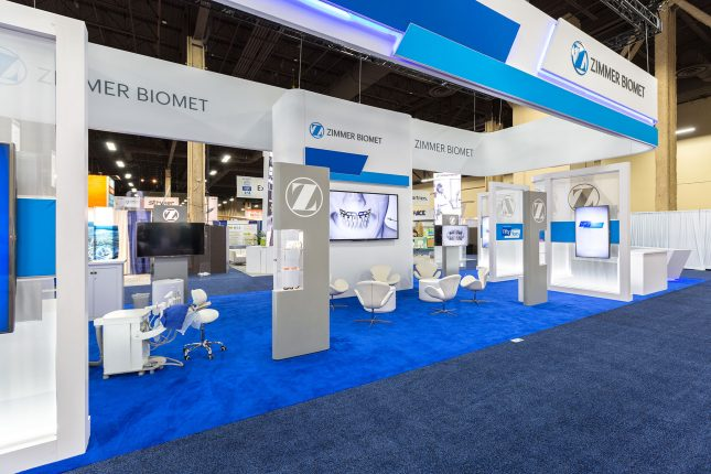 A Trade Show Exhibit with blue carpet, tall and narrow, grey and white vertical display cases, white chairs, and suspended signage.
