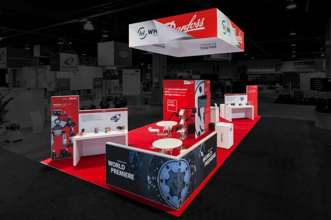 An elevated perspective of a Danfoss White Drive trade show exhibit with red carpet, white tables and counters with multiple red vertical displays throughout and a suspended banner with their logo above and a pony wall with a black and blue print of a gear in the foreground. Photo edited so that the outside area is darkened and colorless.
