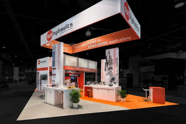 Trade show exhibit with an orange and white color scheme, a suspended rectangular banner with four faces above and multiple product displays within and a two-story platform in the background. Photo edited so that the outside area is darkened and colorless.
