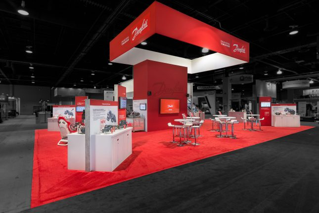 A trade show exhibit from an oblique angle with a red wall in the center, rectangular red banner floating above and red carpet with modern white tables, chairs and kiosks edited so that area outside the booth is darkened and colorless.