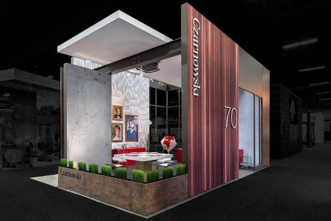 Czarnowski trade show exhibit with a wood-paneled exterior and low decorative planter as an exterior border with classical art on a wall in the background and edited so that the outside area is darkened and colorless.