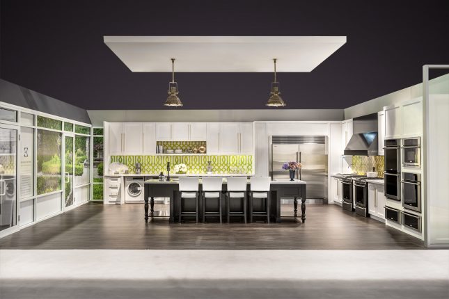A tradeshow exhibit kitchen with white cabinets stainless steel appliances and a black wooden island with a suspended soffit and two gold hanging lamps over greyish brown hardwood floors and below a purple digitally edited ceiling.