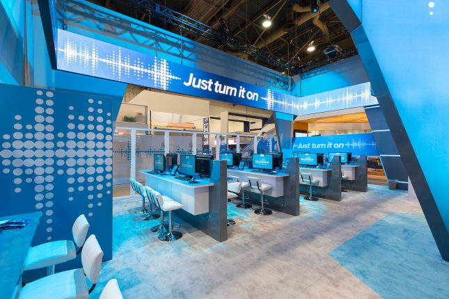 """Four rows of white counters under blue lighting with white padded barstools and video monitors displaying a blue Stockwave logo beneath a thin video wall which surrounds the exhibit displaying the text """"just turn it on""""."""