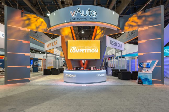 Grey and orange arch elements extending forward from a v-shaped centerpiece with a illunimated welcome counter and vAuto logo suspended above and an orange video screen directly center.