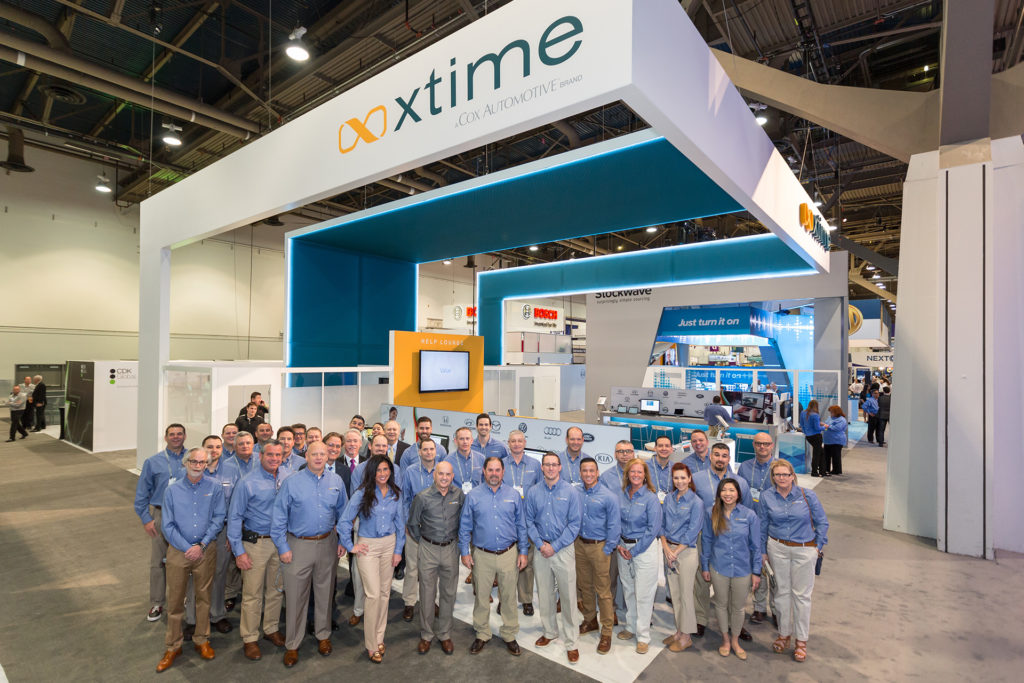 A group of 30 people in blue shirts and khaki pants in front of a trade show exhibit with a suspended white ceiling with the xTime logo above.