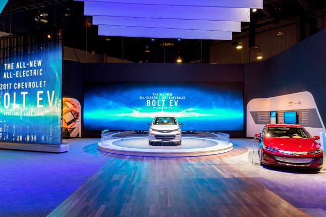 Hardwoode floor leading to a circular pedestal with a grey chevy bolt atop, a a red vehicle to the right and a video wall with ethereal imagery and text in the background.
