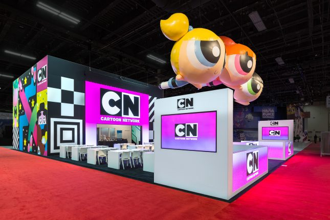 A black and white tradeshow exhibit with three floating inflatable powerpuff girls suspended above and a pink Cartoon Network logo on video screens.