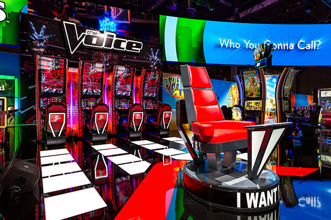The red chair from The Voice in the foreground with The Voice slots in the background at the IGT booth at G2E 2016