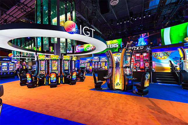The IGT logo on a circular frame surrounding a video chandelier which hangs above slot machines at the IGT booth at G2E 2016