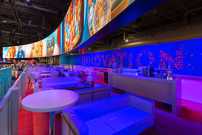 Sofas and tables on an elevated deck beneath a curved video wall at the IGT booth at G2E.