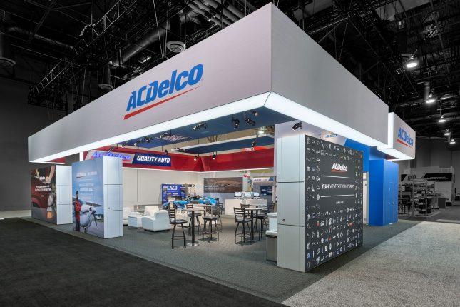 An angular view of the ACDelco tradeshow booth with a suspended grey banner and graphic blocks as walls with barstools, tables, and displays inside.