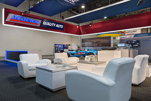 """White sofa seating facing tables with auto parts encased in transparent cubes in the foreground with a red suspeded banner above emblazoned with the ACDelco logo and the words """"Quality Auto""""."""