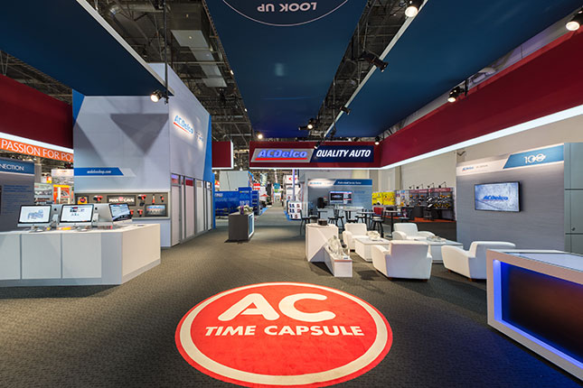 The inside of the ACDelco tradeshow booth with a red circular medallion on the floor, white seating to the right, computer kiosks on the left and in the rear the ACDelco logo suspended on a banner.