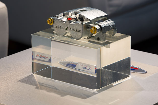 An ACDelco caliper atop a solid transparent cube resembling glass with the ACDelco logo and part numbers etched into the cube.