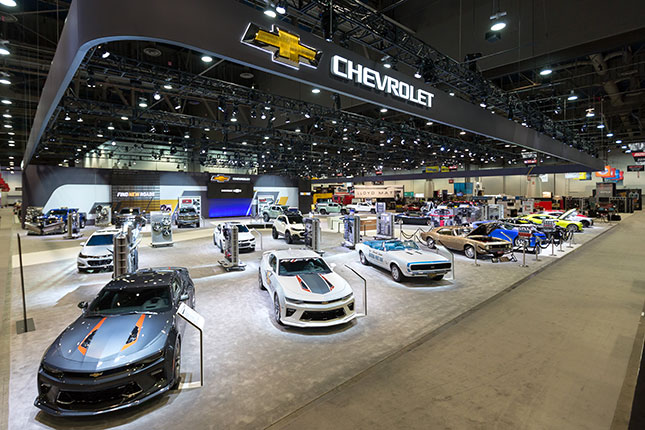 An elevated angular view of the Chevy booth at SEMA with classic Chevy Camaros lined up in the foreground and the Chevrolet logo emblazoned on a dark grey banner floating above.