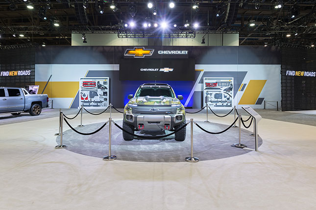 A prototype chevy utility vehicle behind stantions in a grey circular carpeted area with a video screen, two vertical displays with Chevy parts attached and the chevrolet logo in the background.