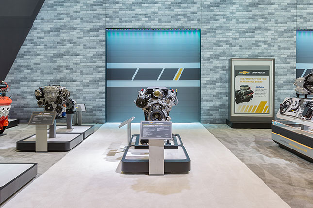 A Chevy engine on a pedestal atop tradeshow carpeting with a fauz brick wall and garage door in the background.
