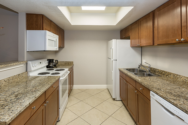 An apartment kitchen with tan tile brown grantie countertops a white range and microwave to the left and a stainless steel sink and white refrigerator to the left.