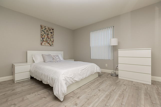 A bedroom with grey walls, hardwood floors, a bed to the left with white sheets and a lamp and white dresser to the left.