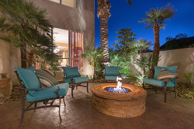 Four metal patio chairs with teal-colored cushions surrounding a fire pit at dusk with palm trees surrounding them and the living room of the home visible through a large window in the background.