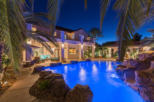 An electric b;ue illuminated swimming pool with rock landscaping and small waterslide visible through palm fronds in the foreground and a two-story home and pool house in the background.