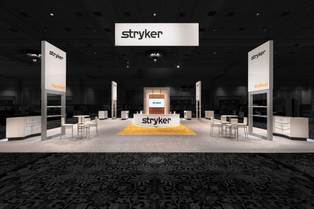 A centered photo of the Stryker booth at ACFAS 2017 with hanging banner, welcome counter with LCD screen, and four vertical signs all with the Stryker logo--edited so that background is dimmed.