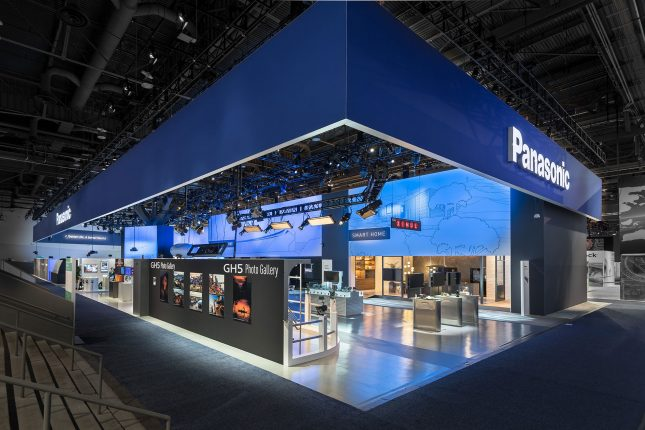 """An angled view of a large trade show exhibit with a blue banner abover with a white """"Panasonic"""" illunimated sign on each side and a blue and white interior with multiple exhibits and displays."""
