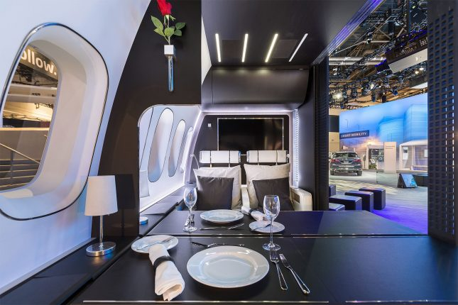 Replica of a First-class aircraft cabin as a CES 2016 trade show exhibit with dinnerware laid out on a black table with white walls shot from the perspective of a seated passenger.