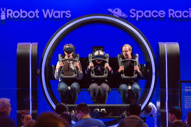 A three-person circular virtual reality ride with two men and an elderly woman seated in the center in front of a blue background which says Robot Wars and Space Racing and a small crowd in front.