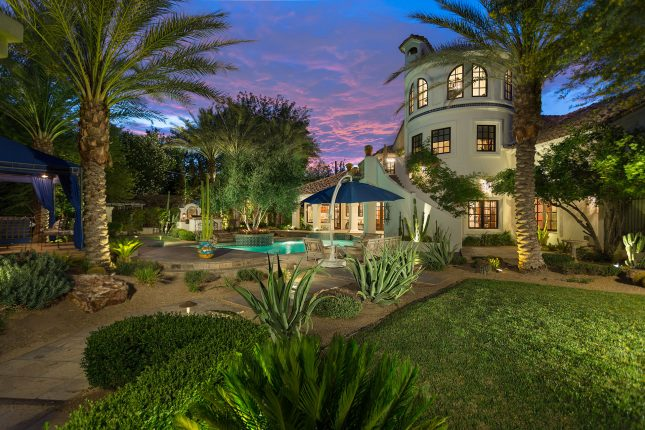 The backyard of a spanish-style villa with grass and desert foliage in the foreground, patio furniture and umbrella in the center and various trees including palm trees throughout and a pool and home in the background amidst a blue-and-red sunset.