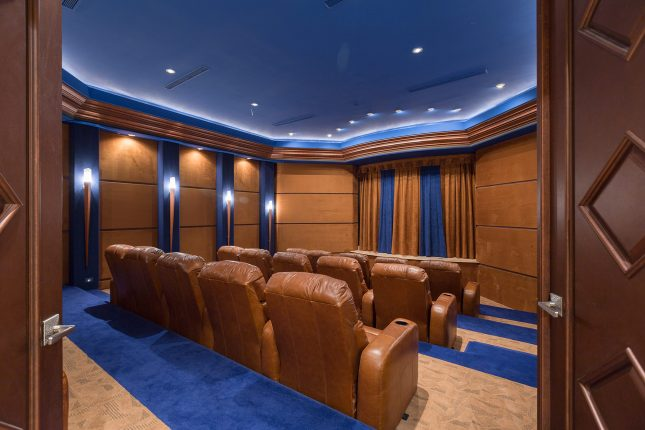 Double doors opening to a home theater with brown recliners, blue ceiling, blue and tan carpet and a blue a brown curtain covering the screen.