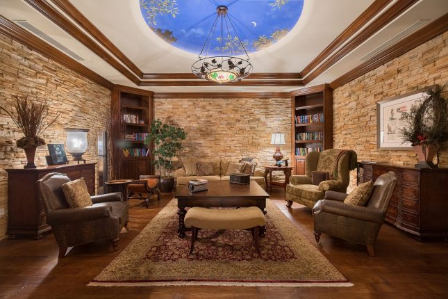 A dark, moody study with a recessed, blue and gold painted recessed medallion and chandelier on the ceiling, slate stone walls, 3 chairs, and dark-wood furniture.
