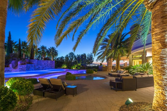 Palm fronds framing the top of a photo of a desert luxury home backyard at dusk with patio chairs, wading pool, lazy river and swimming pool, and view of Las Vegas in the background.