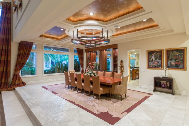 A large dining room with an area rug atop beige tiled floors, and large table with seating for twelve and a stained-glass light fixture hanging from a coffered ceiling with wall-papered inlay and recessed lighting.