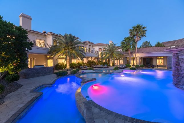 A luxury home backyard at twilight with swimming pool and lazy river in the foreground and palm trees, patio furniture and large home in the background.