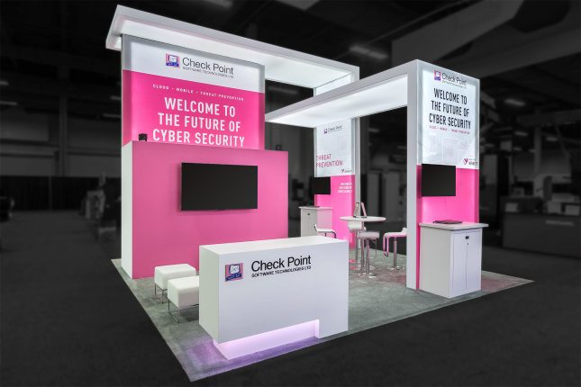A white-and-pink rear-illuminated trade show exhibit with angled wall-and-ceiling panels.
