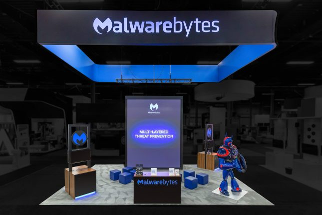 Malwarebytes trade show exhibit with a suspended black banner with rear-illuminated blue logo, and blue interior, a 15-foot tall video display, a black, wood-paneled welcome desk with blue logo on the front and two wood-finished kiosks within the exhibit and a 8-foot blue, red and black robot wielding a shield.