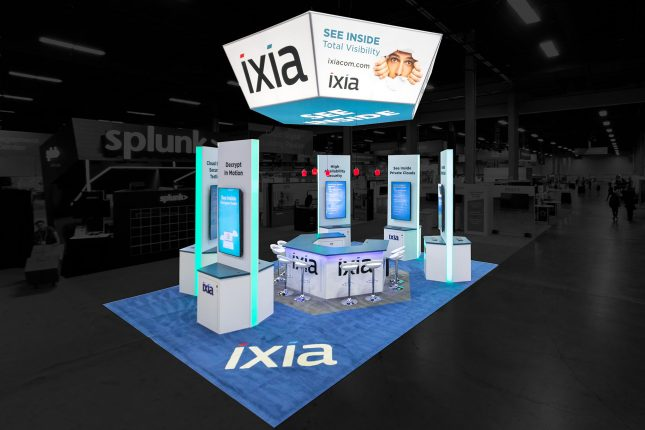 Elevated perspective of Ixia tradeshow exhibit with a white and blue suspended hexagonal banner above five white, tall stations with vertical video screens, a hexagonal counter in the center with modern white barstools and blue carpet with an Ixia logo.