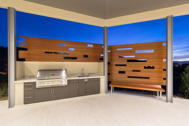 A stainless steel built-in backward bbq with wood-like aluminum fencing and bench atop light beige tiled flooring and a rich blue twilight sky in the background.