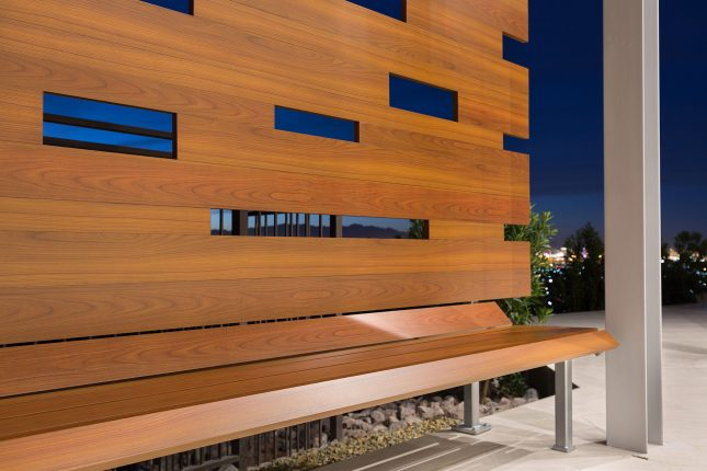 A wood-like aluminum backyard bench on a light beige tiled patio with Las Vegas city lights in the background.