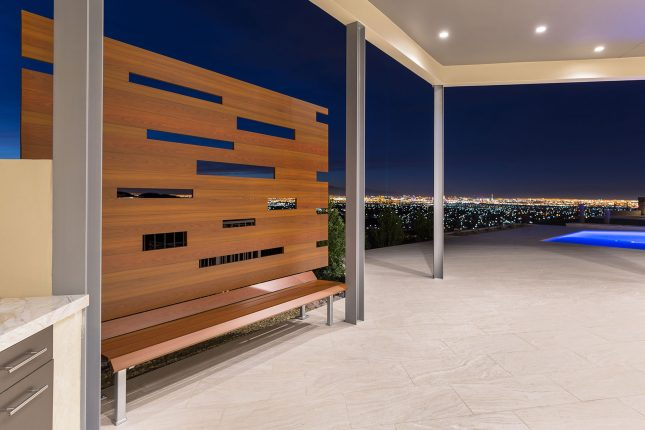 A wood-like aluminum backyard bench on a light beige tiled patio with Las Vegas city lights and a pool in the background.