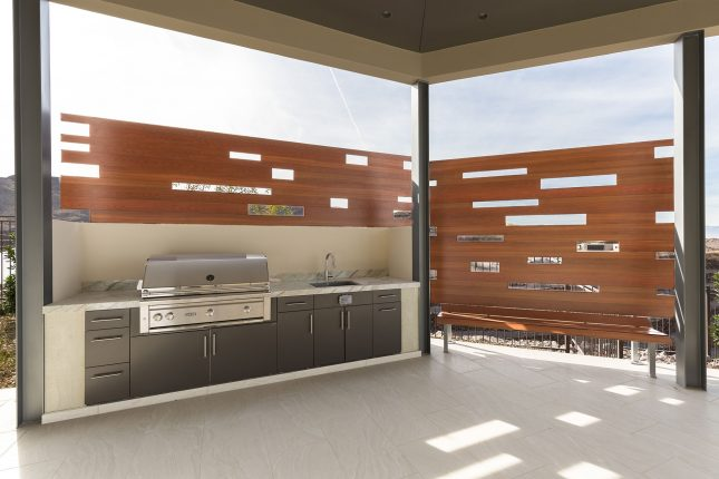 A stainless steel built-in backward bbq with wood-like aluminum fencing and bench atop light beige tiled flooring with cloudy bright daylight in the background.