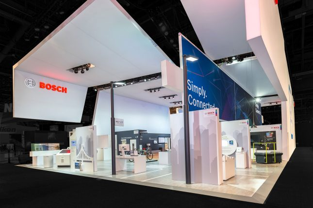 A large Bosch tradeshow exhibit made of suspended white panels and multiple kiosks with the red Bosch logo on the top left.