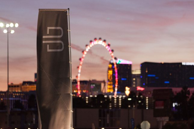 The white B of the Byton logo on a grey banner flapping in the wind in front of the High Roller Ferris Wheel and Casinos of the Las Vegas Strip at dusk.